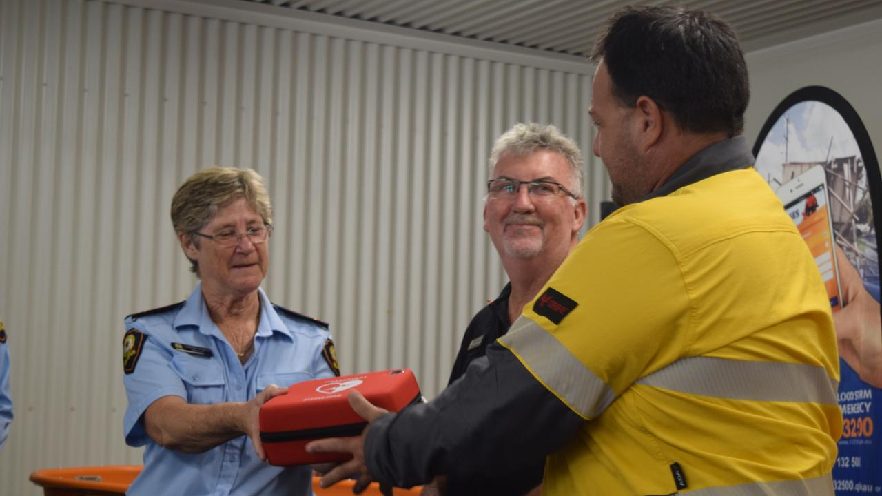 Christine Persello from Bowen SES and Whitsunday SES local controller Mark Connors accept a new defibrillator from Ergon Energy acting area manager Damian Pennisi. Photo: Elyse Wurm