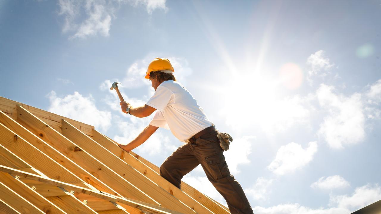 roofer carpenter working on roof