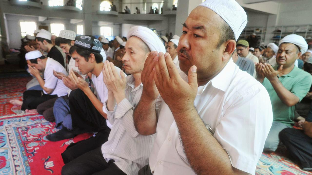 Uighur men pray in a mosque which opened amid the city wide closure of the mosques in Urumqi in western China's Xinjiang province 10/07/2009.
