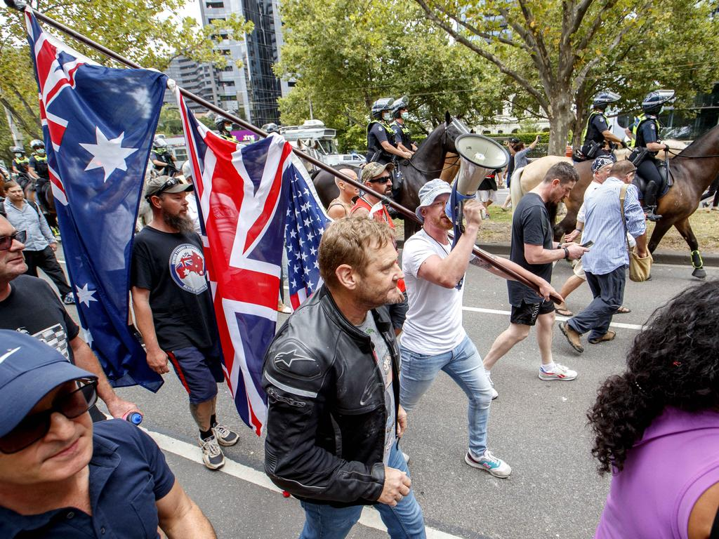 Protesters march past police at an anti-vaccination protest in Melbourne on Saturday afternoon Picture: NCA NewsWire / David Geraghty