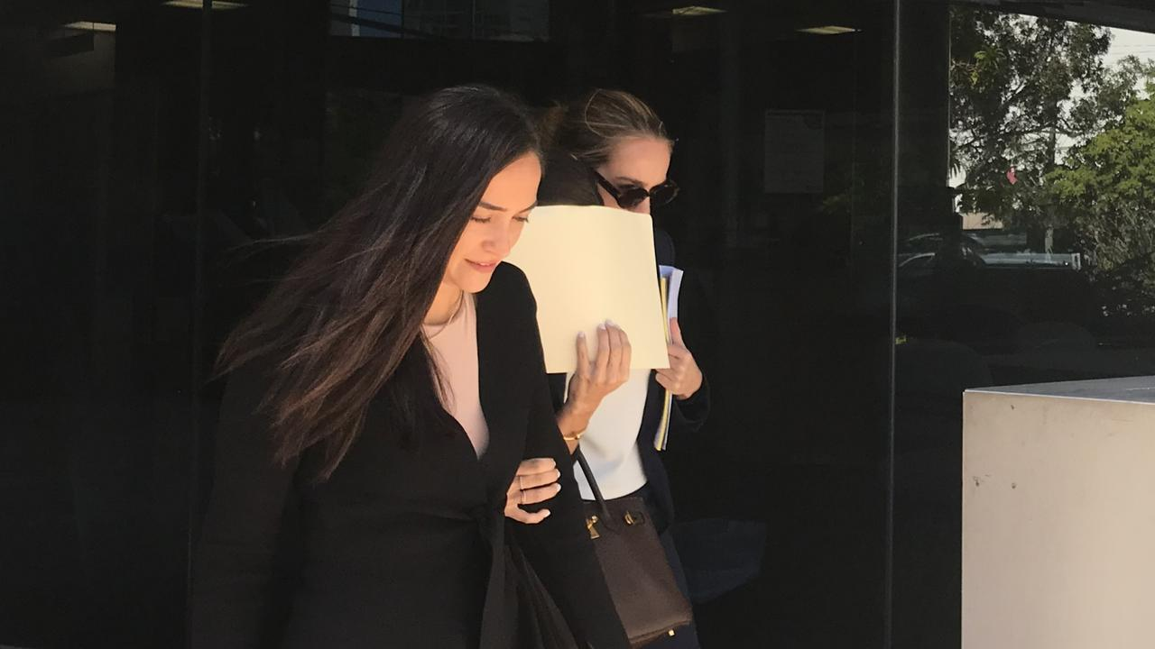 Rebecca Jane Klodinsky, hiding her face behind a manilla folder, pleaded guilty to stealing in the Southport Magistrates Court. Picture: Jodie Callcott.