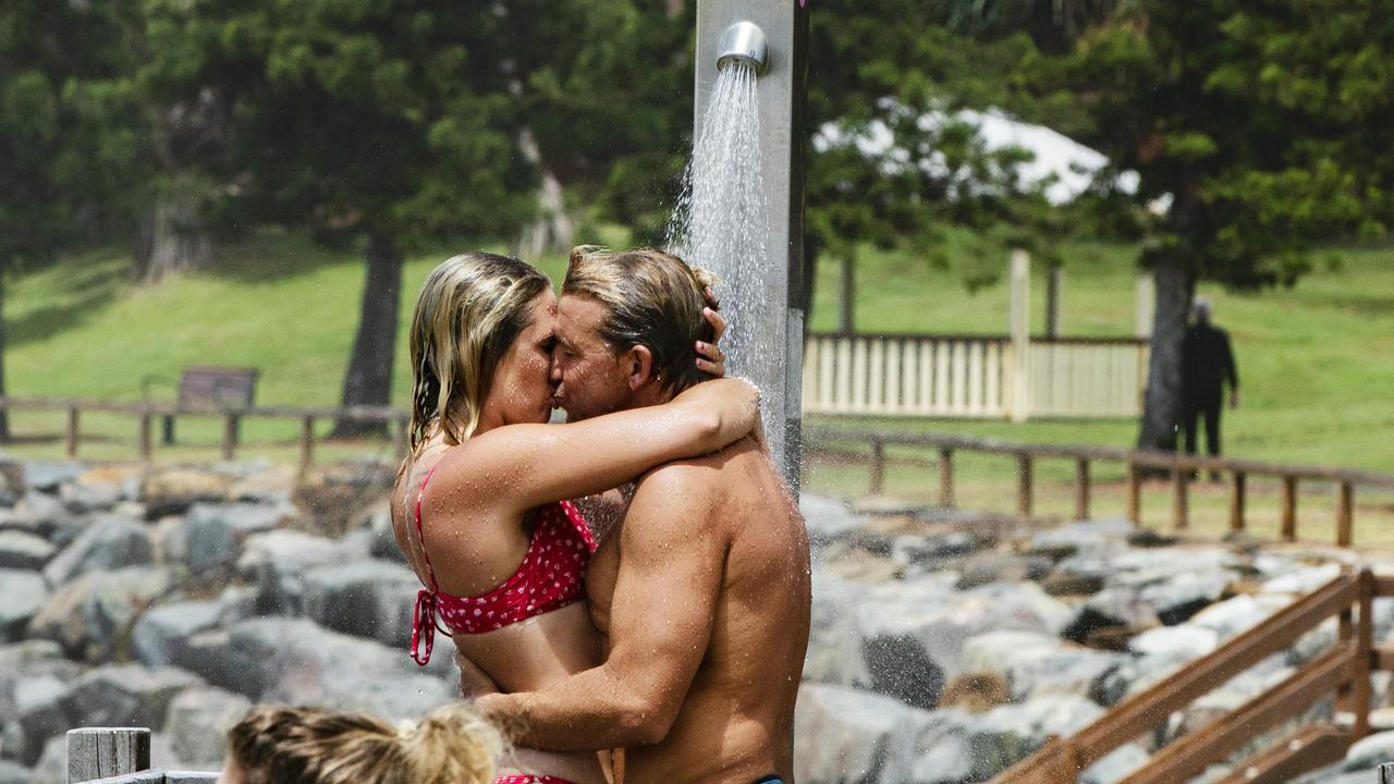 A pair of lovers find a way to warm up on a wet and rainy day at Moffat Beach at the weekend. Picture Lachie Millard