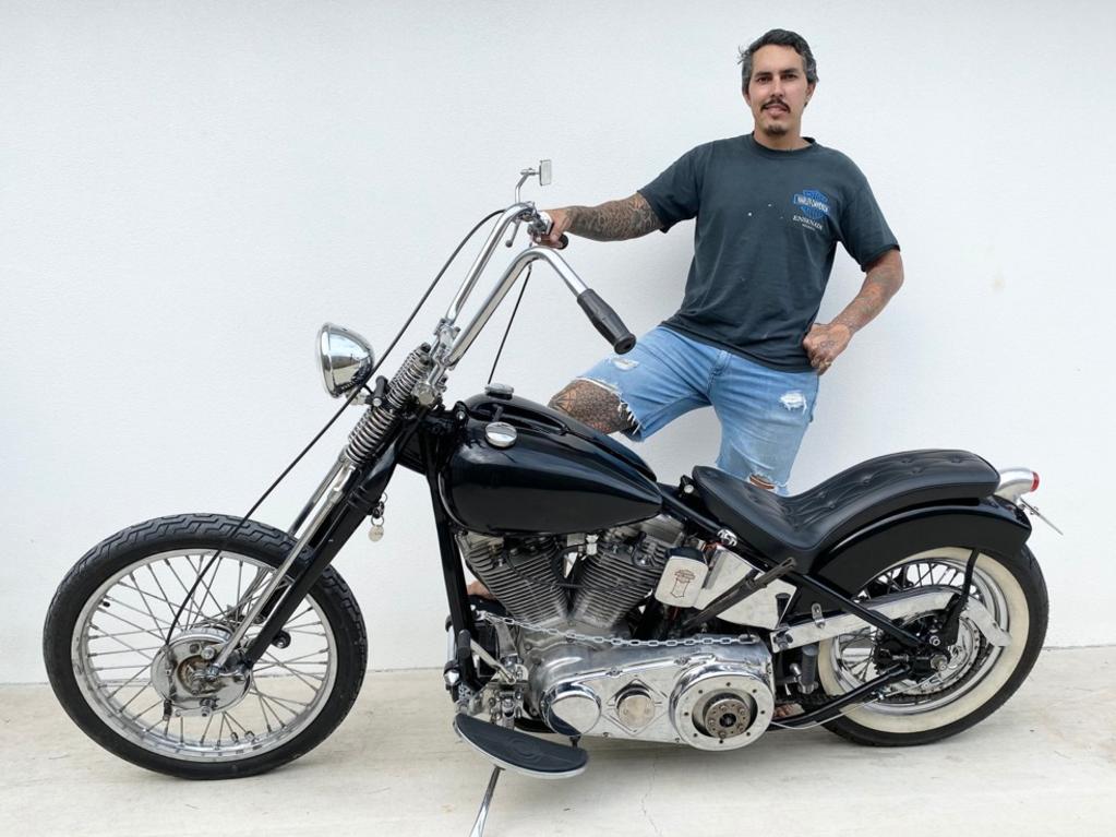 Townsville army veteran Adam Barrett shows off his rebuilt his Harley chopper.