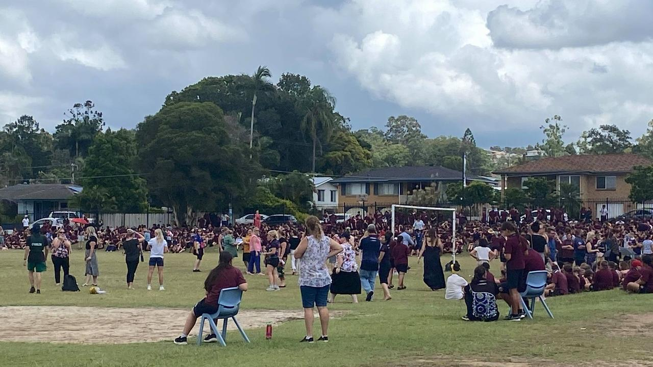 Staff and students at Ipswich State High School evacuate to the oval.