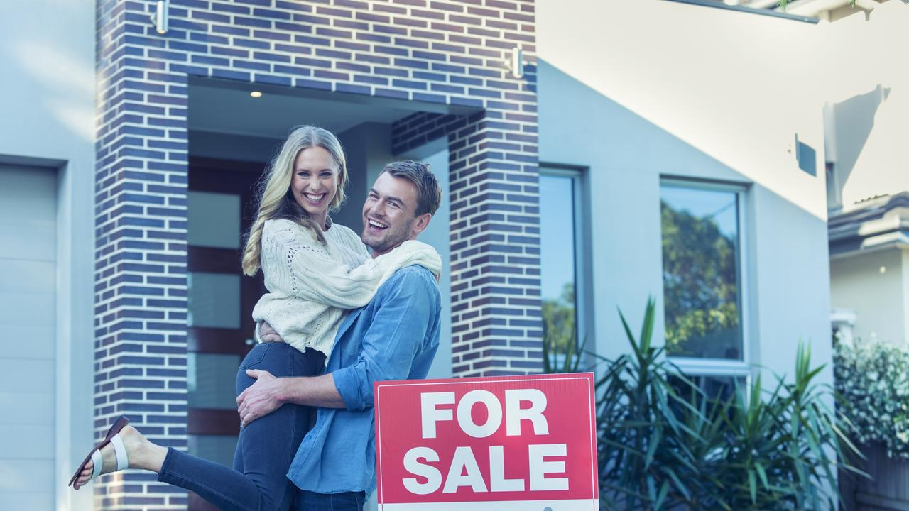 A couple celebrate purchasing their first home.