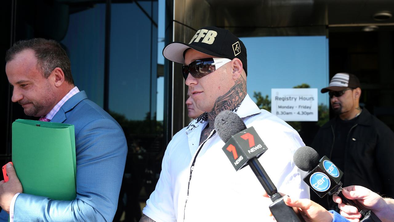 Bikie Ricky Chapman (right, in white shirt) with his lawyer. Picture: AAP