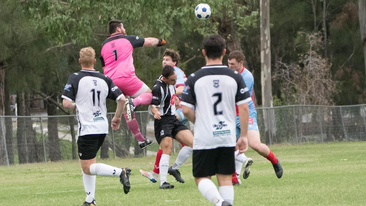 Ipswich City Bulls goalkeeper Brent Witney flies high to punch away the ball in the trial against the Ipswich Knights. Bulls defenders Kurt Neuendorf and Quentin Dodd look on. Picture: Gary Reid