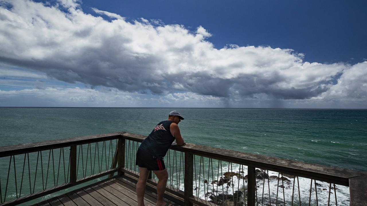 A tourist watches as a rain clouds go out to sea from Point Perry at Coolum Beach. Picture: Lachie Millard