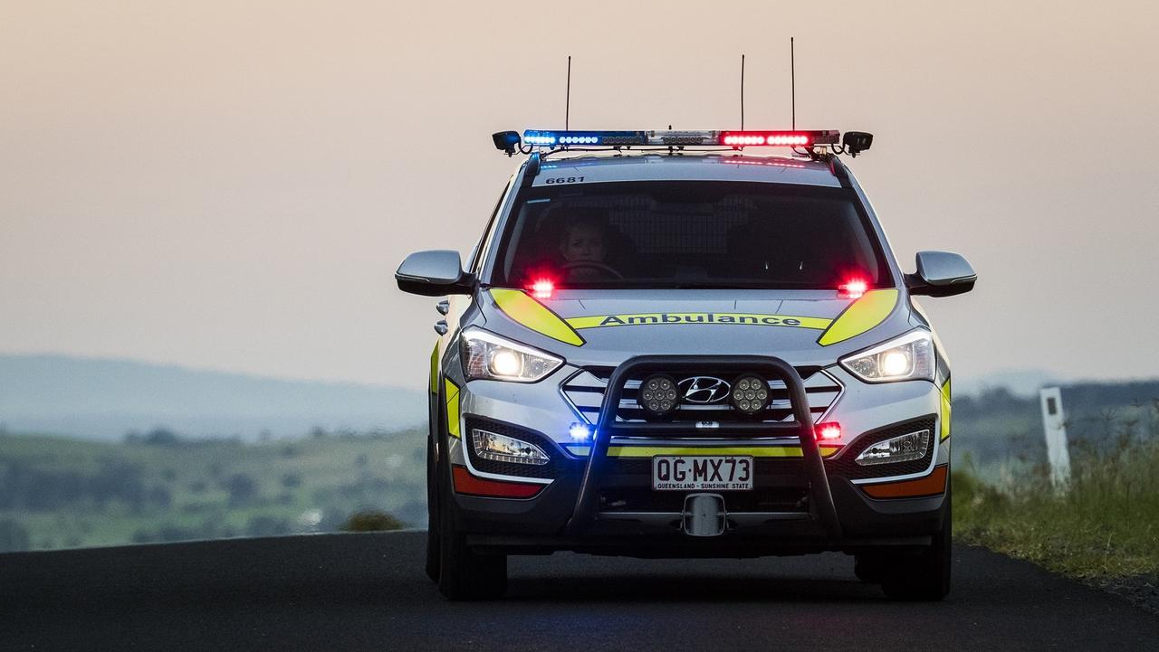 Queensland Ambulance Service paramedics a treating a man injured in a single-vehicle crash.