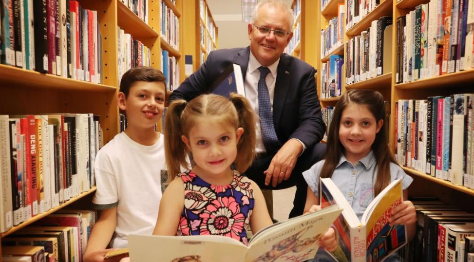Prime Minister Scott Morrison helps Tom Panozzo, 9, Lily Maher, 7, and Charlotte Maher, 9, practice their words ahead of the Spelling Bee. Picture: Adam Taylor