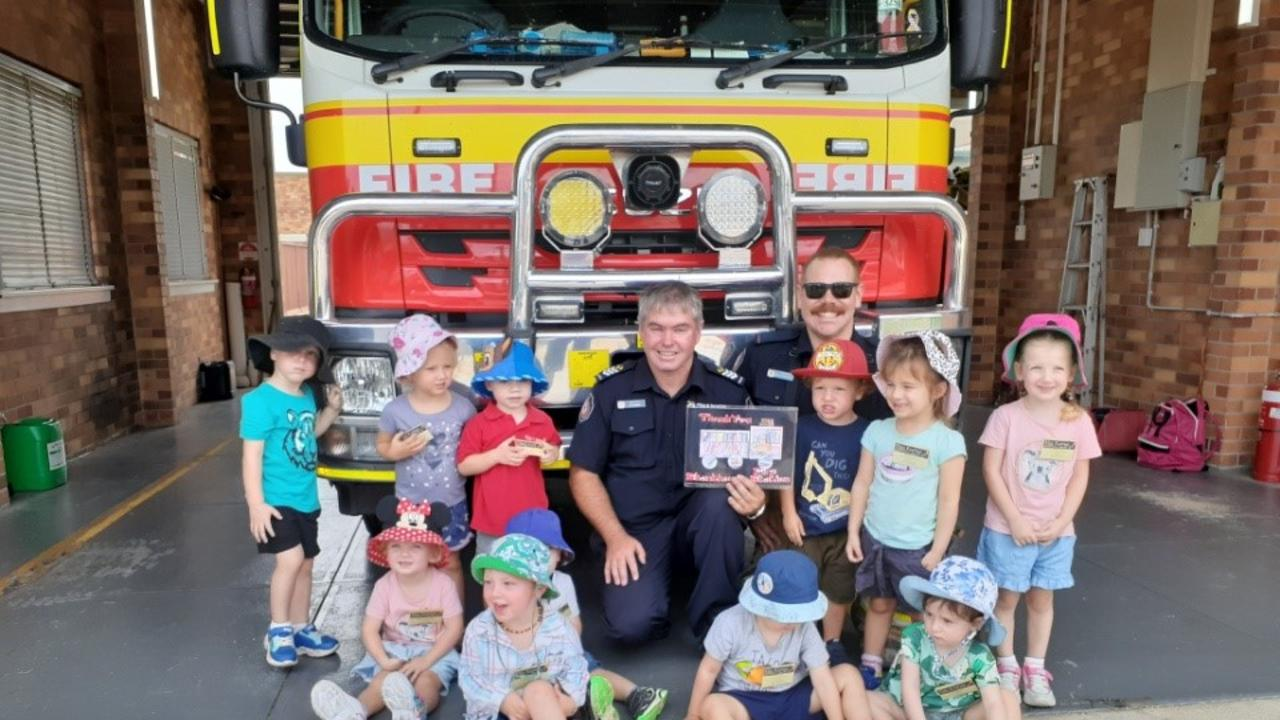 Stanthorpe Fire and Rescue Auxiliary Captain Ian Barnden and Auxiliary firefighter Reece Lancaster-Kelly with the kids from Kids Korner Child Care. Picture: QFES