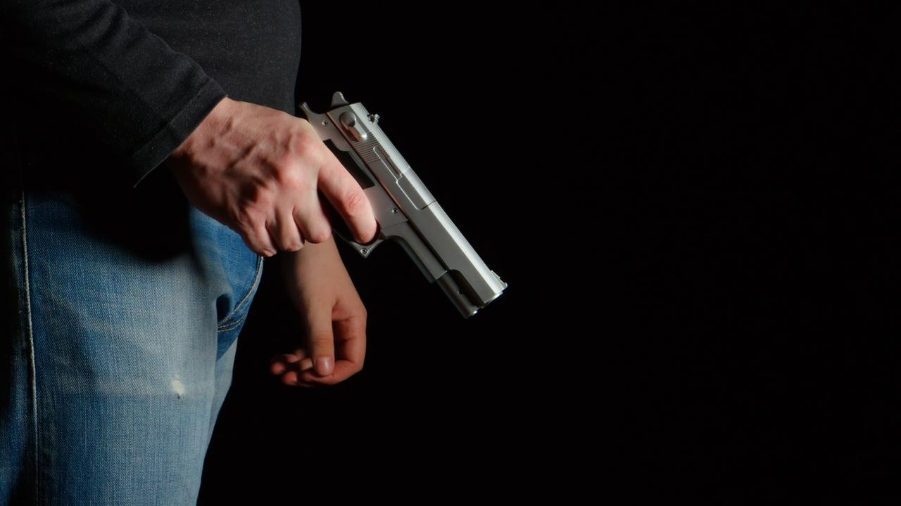 GENERIC PICTURE: Man with a gun in a dark room, man holding gun