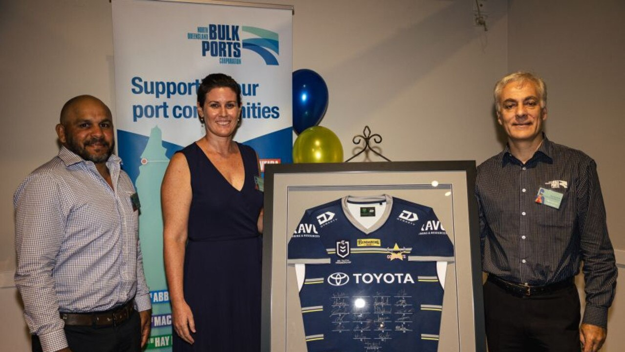 The Neighbourhood Hub's Claire Christensen accepted a signed 2021 Cowboys jersey from NQBP CEO Nicolas Fertin and Cowboys legend Matthew Bowen to help with future fundraising efforts.