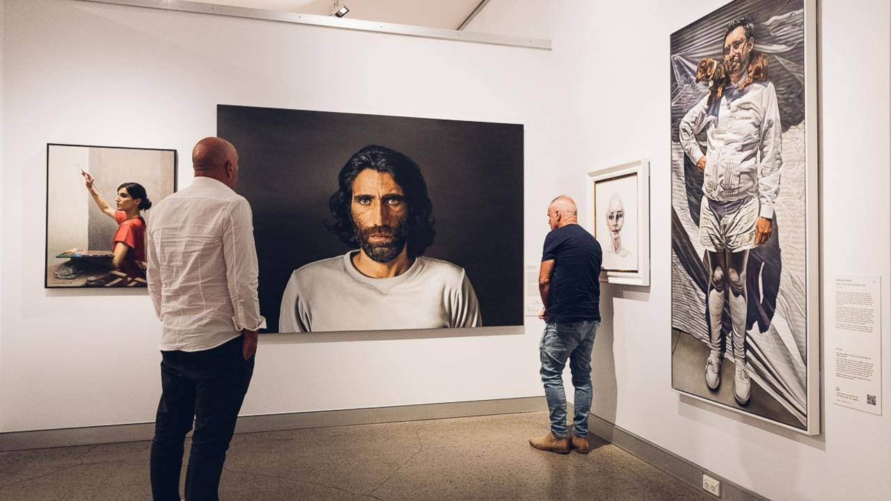 Visitors viewing the portrait of Behrouz Boochani by artist Angus McDonald.