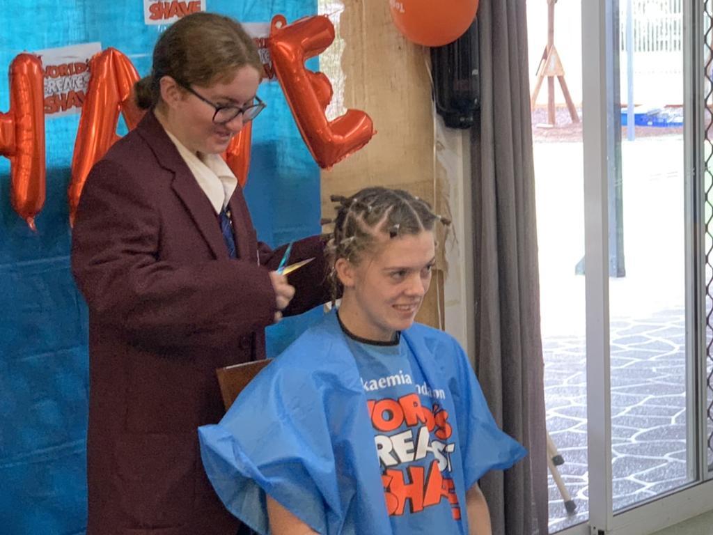 Music star and St John's student Maddy Thomas cutting Remi's last braid. Photo: Lachlan Berlin
