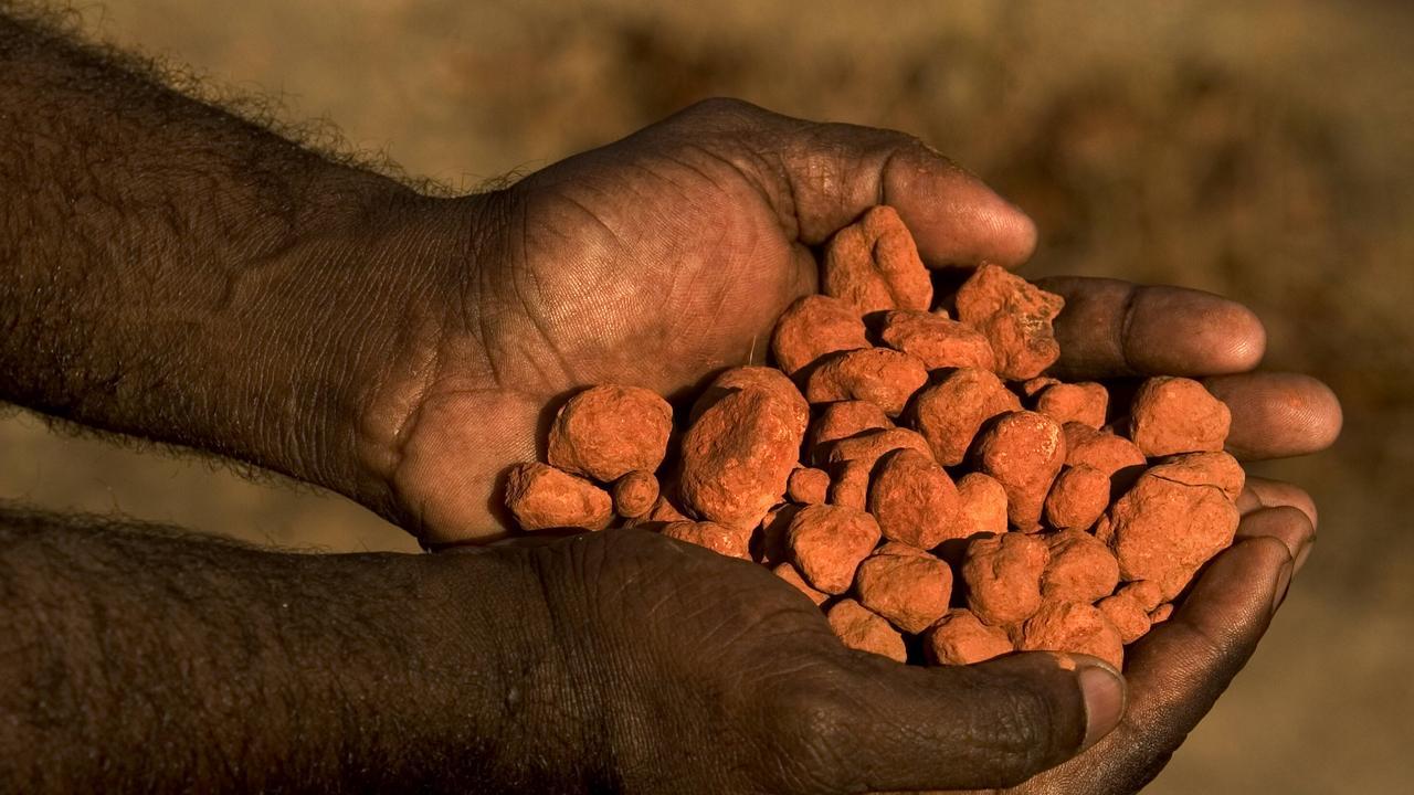 Bauxite in the hands of former Aurukun Mayor Neville Pootchemunka, on the Aurukun aboriginal reserve, western Cape York, Queensland.