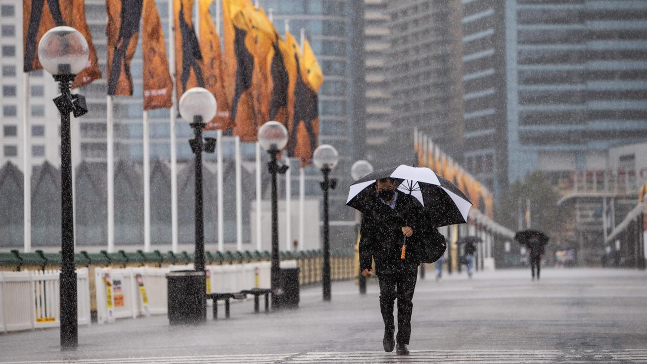 A few hardy pedestrians make their way across Pyrmont Bridge on Friday. Picture: Julian Andrews