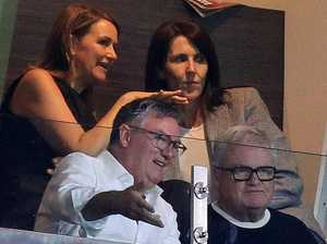 Who was Eddie sitting with at the footy?