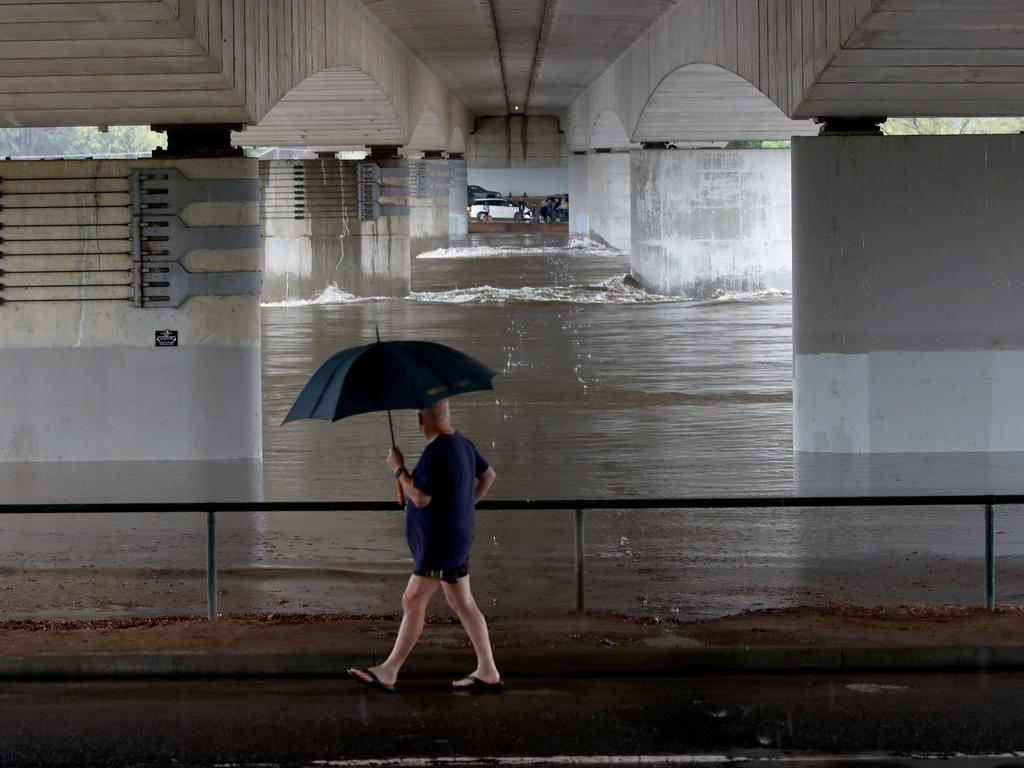 A man holds an umbrella as he looks at the rising flood waters under the Nepean Bridge at Regentville. Picture: Toby Zerna