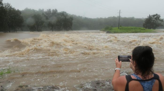 Oxenford local Cheryl Glanz records the floodwater pour over the Oxenford Weir. Picture: Glenn Hampson