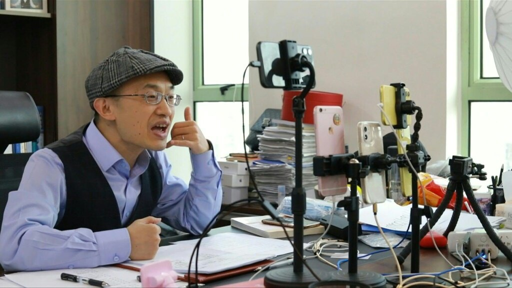 Zhu Shenyong livestreams advice over several phones simultaneously to an attentive audience keen to save their relationships.