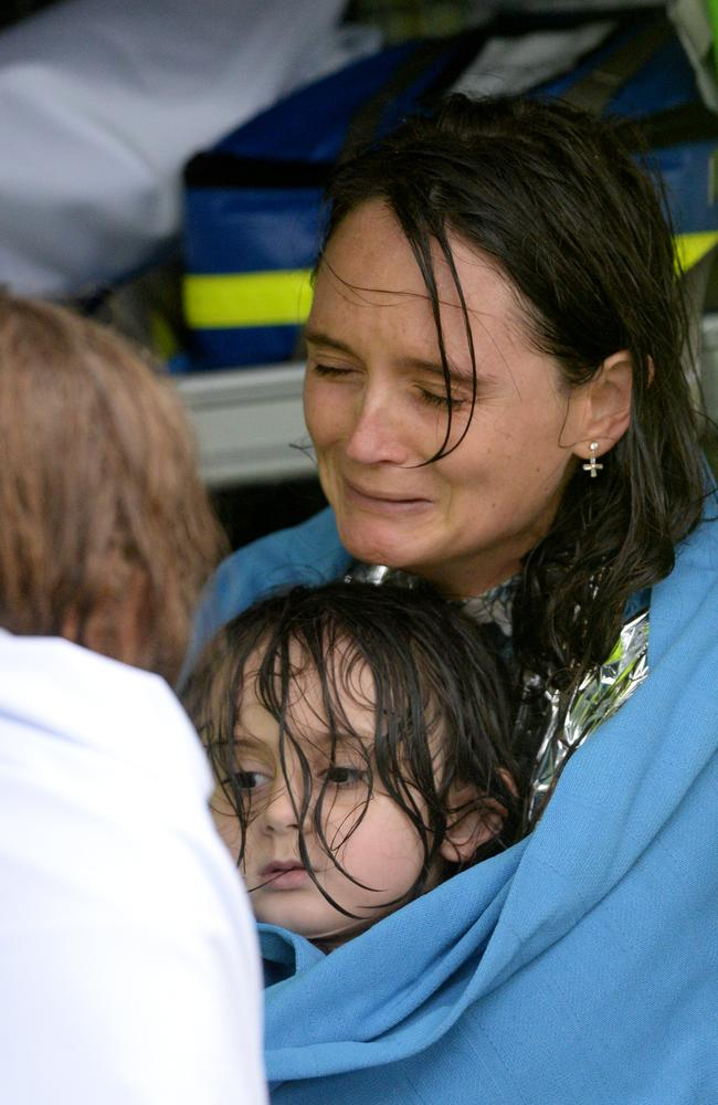 A mother cries tears of relief as she is rescued for a second time, as the rescue vessel capsized after they were initially rescued from their home. Picture: NCA NewsWire/Jeremy Piper
