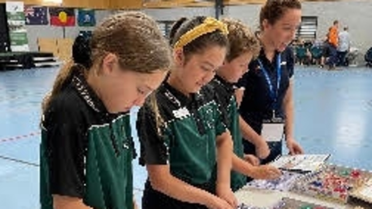 Moranbah State School students Layla White, Sherriah Sterritt and Branden Smallhorn making light work of the 'snap circuit' activity, learning how to put together an electrical circuit by linking the correct pieces to a battery pack, which makes a circuit to create light and power a fan.