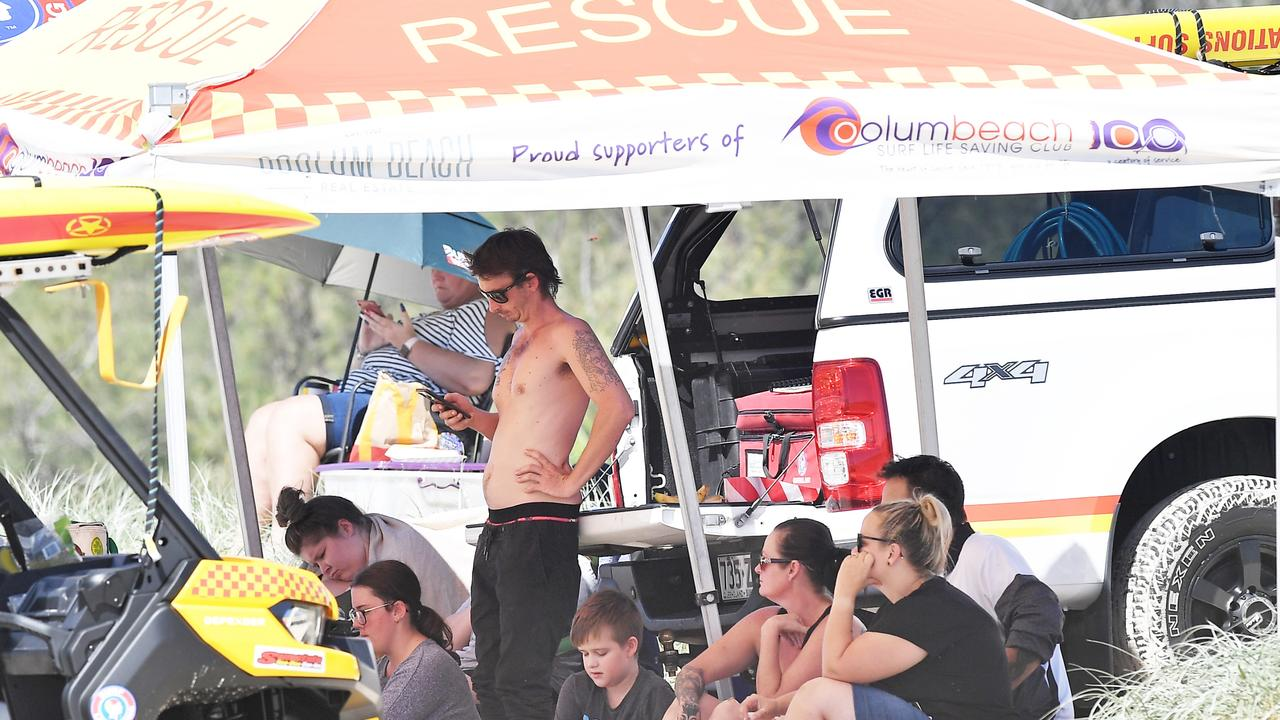 Family and friends wait near the entrance of Stumers Creek on Sunday while a search for a missing Brisbane man continued. Picture: Patrick Woods.