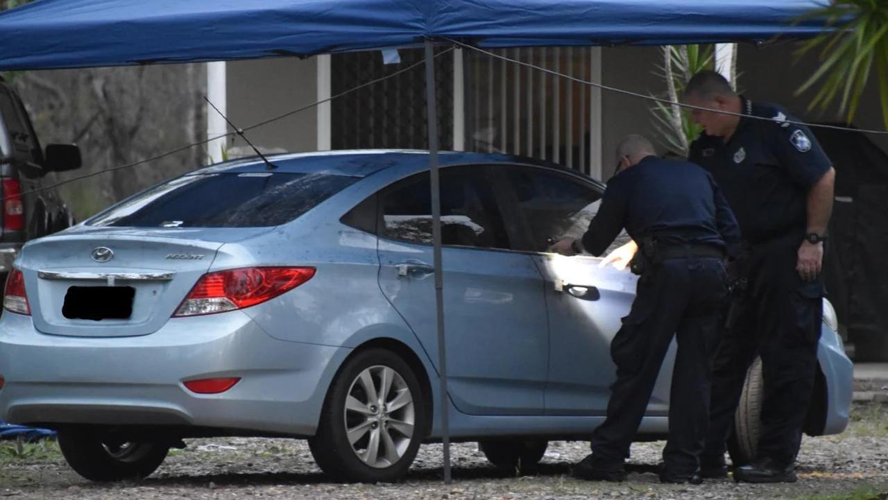 Police examine a blue sedan at the scene.