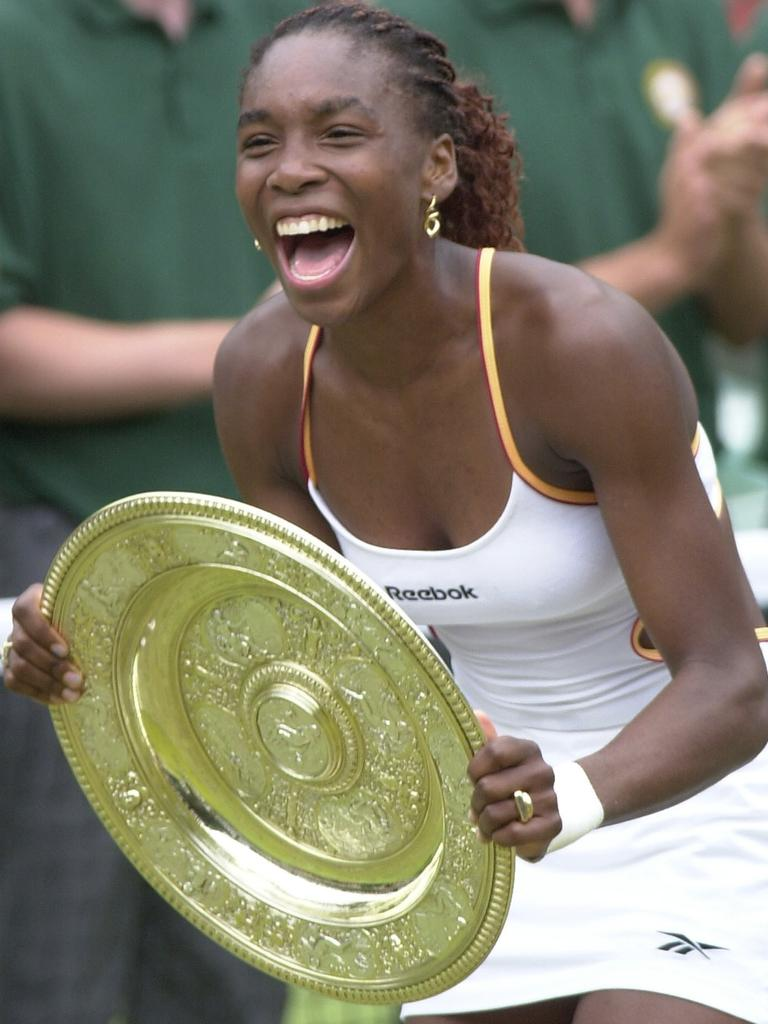 Williams laughs as she holds the trophy after beating Lindsay Davenport.