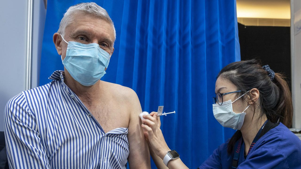 Prof Grant McArthur receives a COVID vaccine from nurse Serena Lin. Picture: Jake Nowakowski