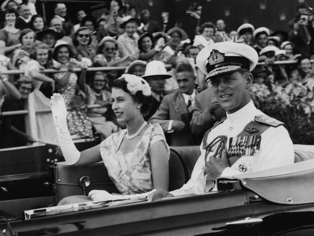 Queen Elizabeth II and Prince Philip wave from an open carriage as they drive past crowds of spectators at the Exhibition Grounds in Brisbane to watch a display of native dances in March 1954. Picture: Paul Popper/Popperfoto/Getty Images