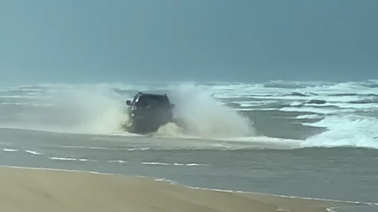 A driver steers into the waves on Fraser Island.