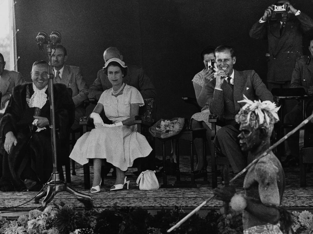 Queen Elizabeth II and Prince Philip (laughing) watch an aboriginal display and wallaby dance at the Exhibition Grounds in Brisbane, during the royal tour of Australia in March 1954. Picture: Paul Popper/Popperfoto/Getty Images