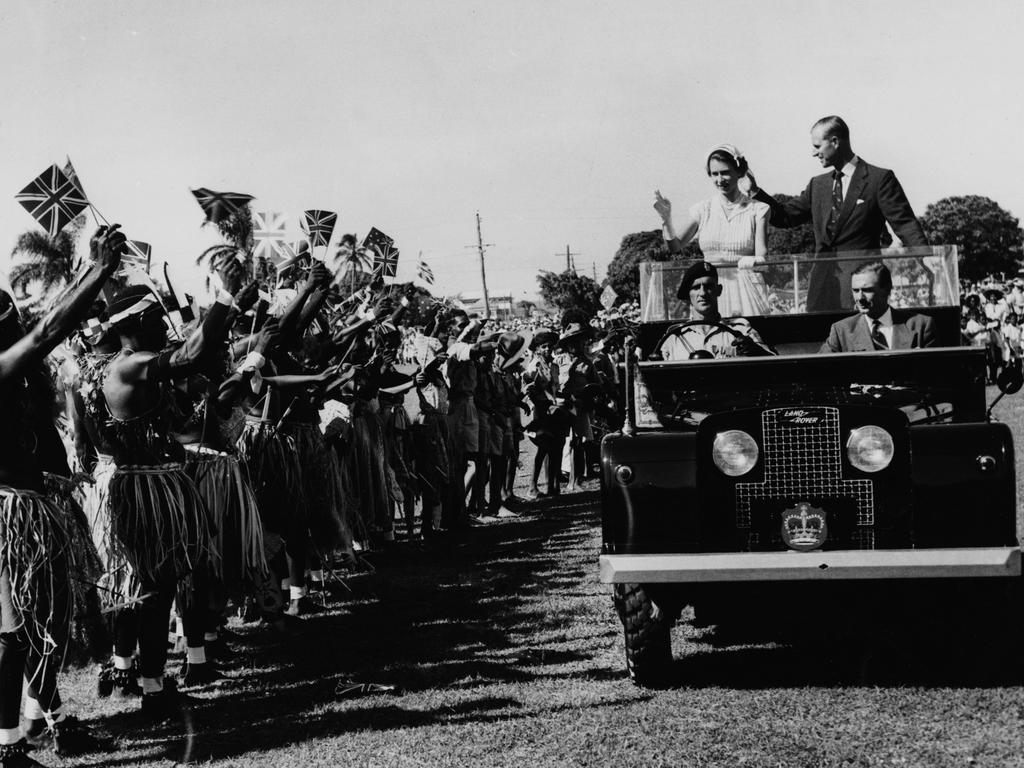 Queen Elizabeth II and Prince Philip wave to a group holding up Union Jack Flags, as the royal couple stand in the back of the Royal Land Rover in Townsville, Australia in March 1954. Picture: Paul Popper/Popperfoto/Getty Images