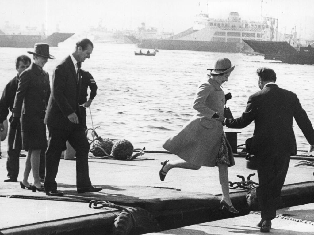 Queen Elizabeth II being helped ashore followed by Prince Philip during their Royal Visit to Australia in 1970.