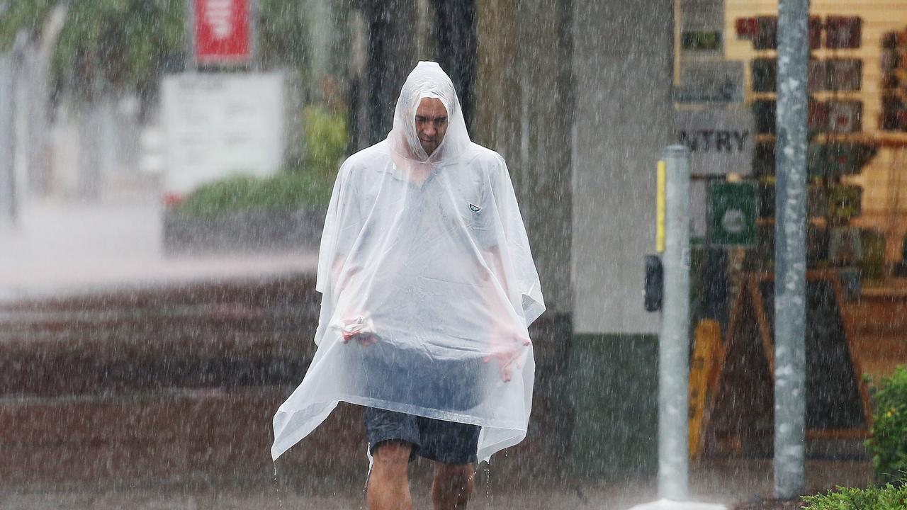 Heavy rain has been falling across Cairns and the far north. Anthony Schaeffer does his best to stay dry in the wet weather while crossing the road at Spence Street in the Cairns CBD. Picture: Brendan Radke