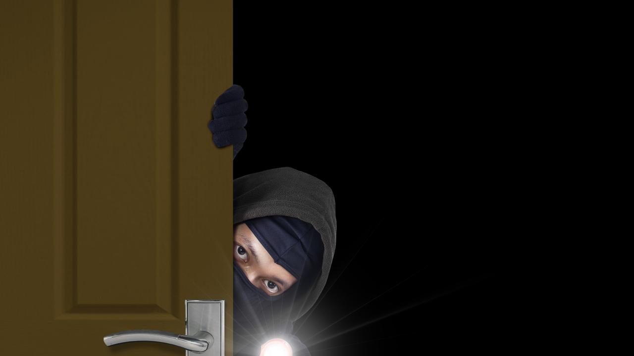 Burglar sneaking in a open house door during a break and enter past security locks and alarms, theft generic