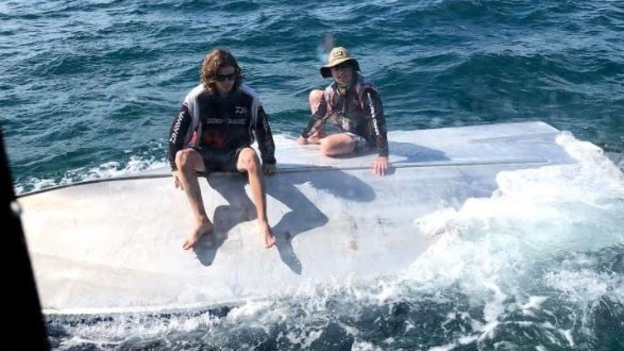 Four men found clinging to the hull of a 6.1m boat have been rescued by the Tin Can Bay Coast Guard crew.
