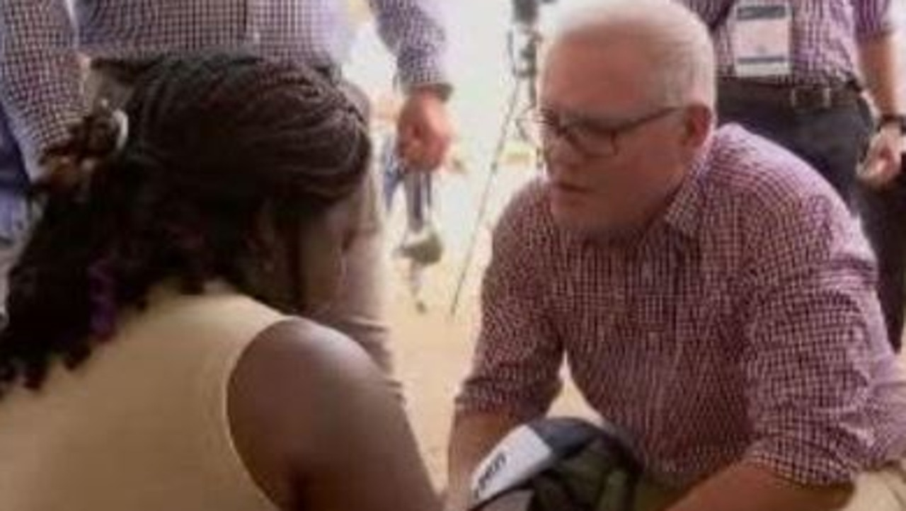 Prime Minister Scott Morrison talks to a woman who begged for help for her family in Africa.