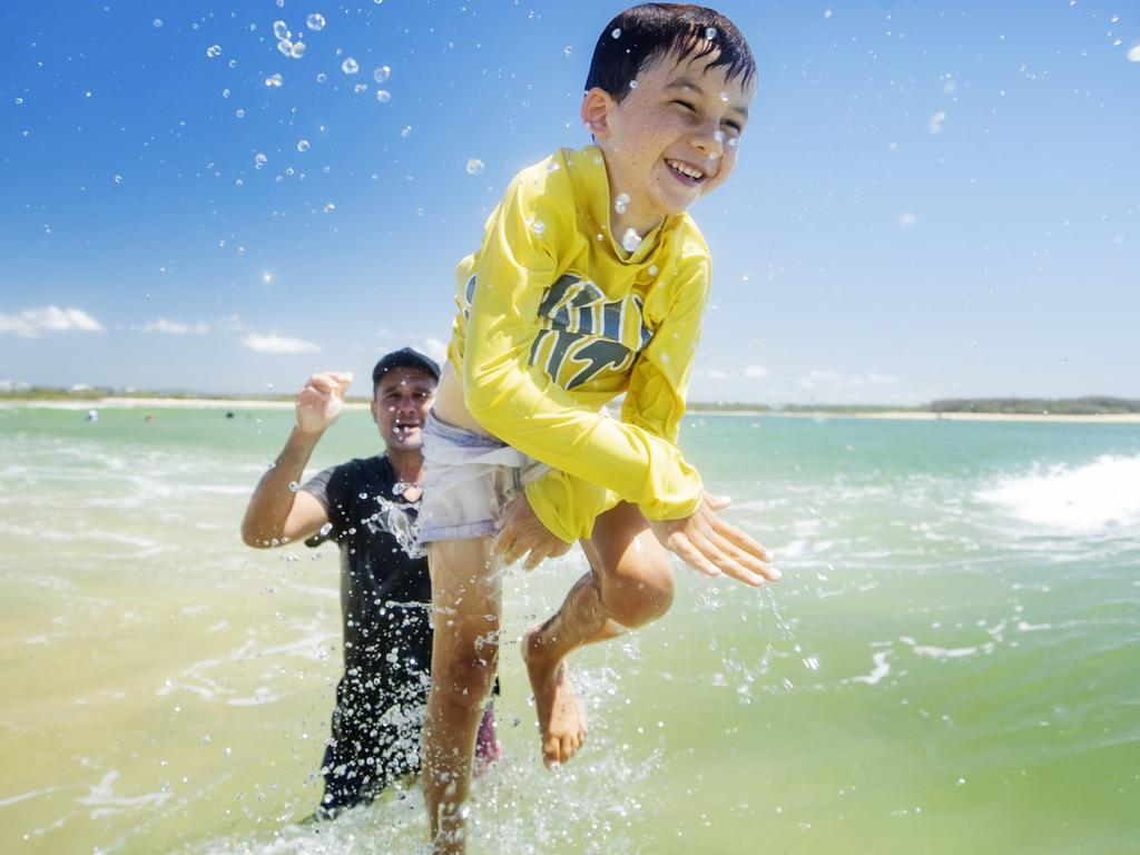 Levi Roth, 7, cools off at Cotton Tree with dad David. Picture: Lachie Millard