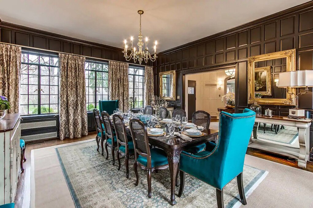 """The dark-wood panelled dining room seats 12 with teal suede chairs and large windows. Picture: <a href=""""http://go.nypost.com/?id=93051X1547088&amp;isjs=1&amp;jv=15.1.0-stackpath&amp;sref=https%3A%2F%2Fnypost.com%2Farticle%2Fjulian-price-house-hillside-hoarders-nightmare%2F&amp;url=https%3A%2F%2Fwww.airbnb.com%2Frooms%2F32381649%3Fsource_impression_id%3Dp3_1618501305_f3IR3CcDqfXkL125%26guests%3D1%"""