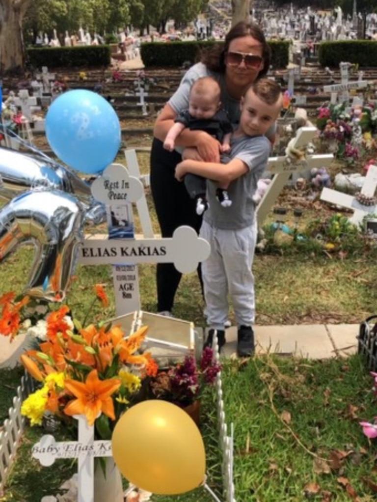 Elizabeth Kakias with baby Alexander and son Romeo at Elias's grave.