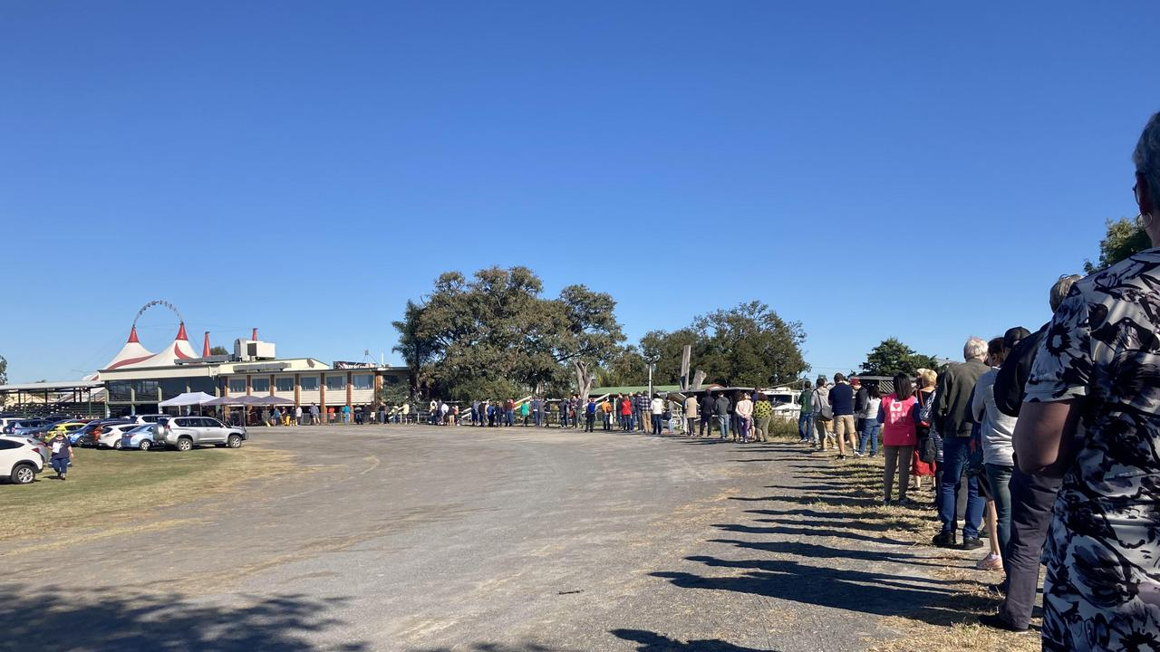 The line up for the COVID-19 jab at the Rocklea Showgrounds on Saturday morning. Picture: Lilian Molina
