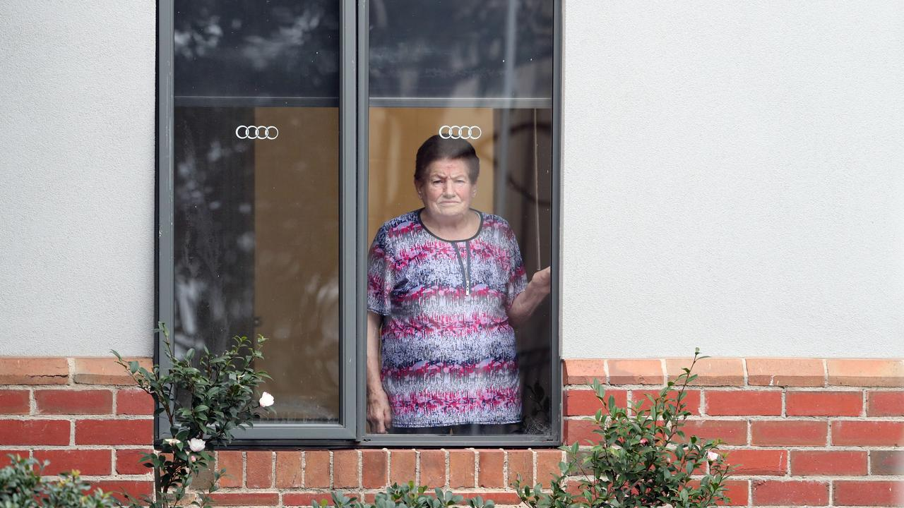 A resident looks out her window at Arcare Maidstone Aged Care after a resident tested positive. Picture: David Crosling