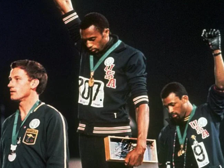US athletes Tommie Smith (centre), and John Carlos make their famous salute alongside Australian Peter Norman at the 1968 Olympic Games.Source:Supplied