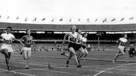 Betty Cuthbert of Australia (centre) runs past the finish line to win the women's 100m at the 1956 Summer Olympics.