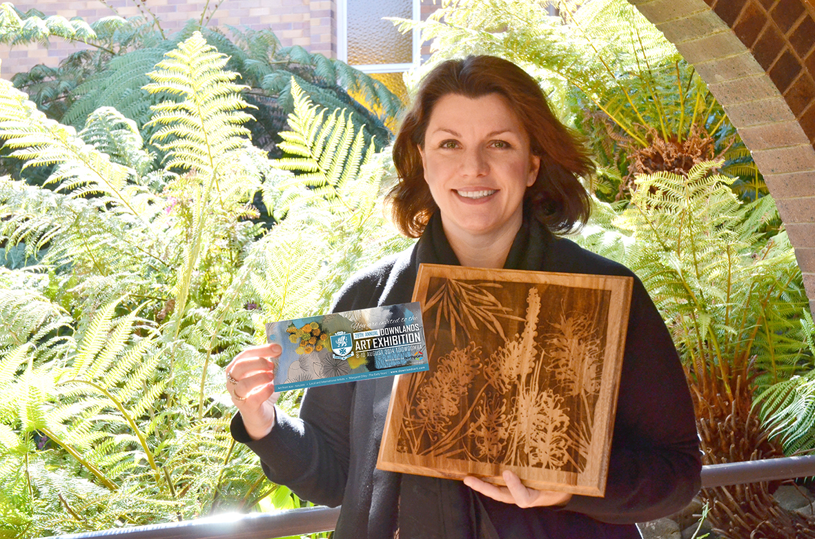 Anna Bartlett holding an invitation and rubbing plate featuring art by Tiel Seivl-Keevers for the Downlands Art Exhibition