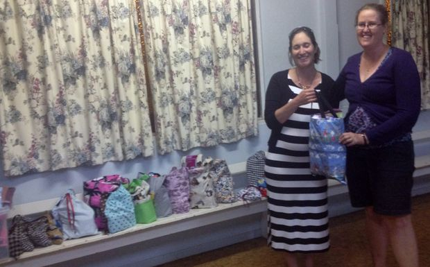Kingaroy Twilight Branch President presenting pack to Uniting Care Community Program Manager, Sarah Franciose-Jones.