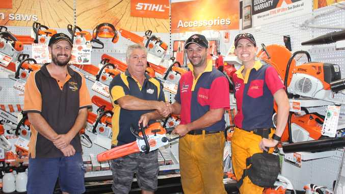 Sean Strenzel on behalf of Yeppoon Small Motor Service, and Grant and April Western on behalf of Cawarral Rural Fire Brigade  handing over the prize chainsaw to the raffle winner, Tony Lawton of Rockhampton.